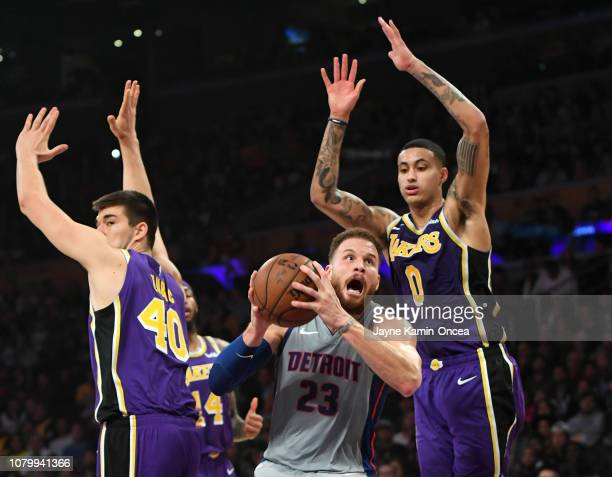 Ivica Zubac of the and Kyle Kuzma of the Los Angeles Lakers guard Blake Griffin of the Detroit Pistons as he drives to the basket in the first half...