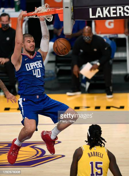 Ivica Zubac of the LA Clippers dunks in front of Montrezl Harrell of the Los Angeles Lakers during the season opening game at Staples Center on...