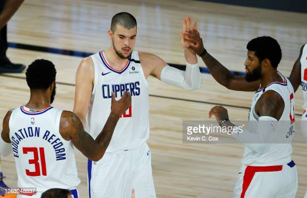 Ivica Zubac of the LA Clippers is congratulated by teammates Marcus Morris Sr. #31 and Paul George against the New Orleans Pelicans at HP Field House...