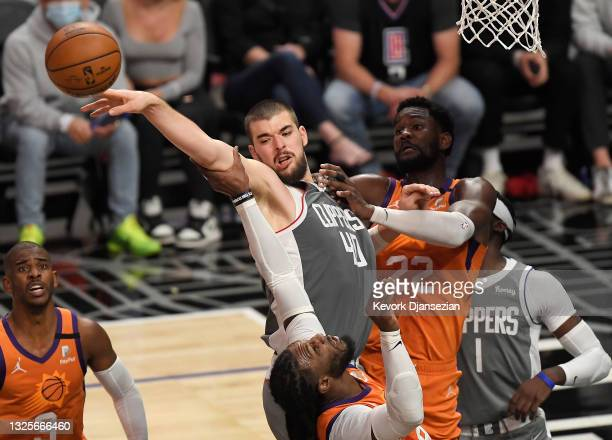 Ivica Zubac of the LA Clippers is defended by Jae Crowder and Deandre Ayton of the Phoenix Suns during the second half in game four of the Western...