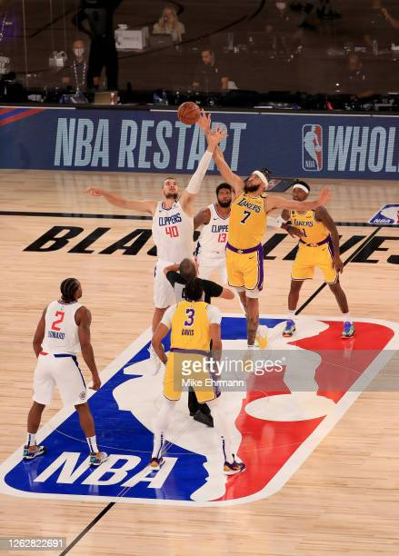 Ivica Zubac of the LA Clippers jumps for the ball against JaVale McGee of the Los Angeles Lakers to start the first quarter of the game at The Arena...