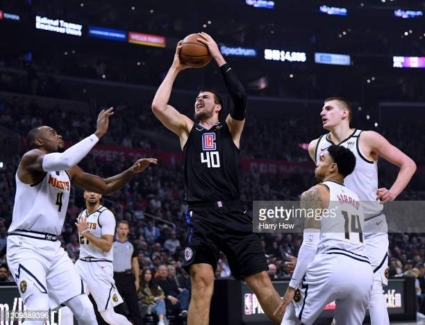 Ivica Zubac of the LA Clippers reacts as he is fouled between Paul Millsap Nikola Jokic and Gary Harris of the Denver Nuggets during the first half...