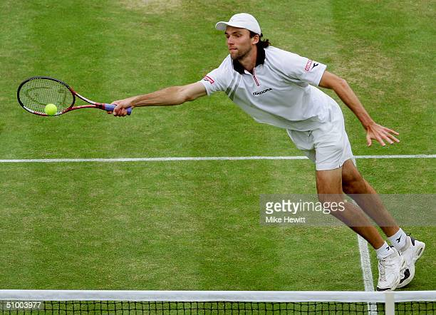 Ivo Karlovic of Croatia in action during his fourth round match against Roger Federer of Swizerland at the Wimbledon Lawn Tennis Championship on June...