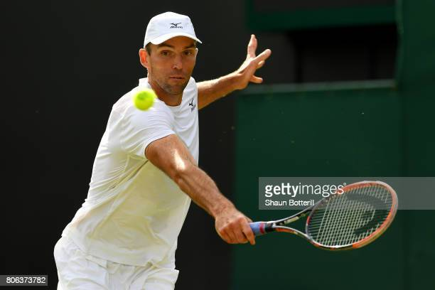 Ivo Karlovic of Croatia plays a backhand during the Gentlemen's Singles first round match on day one of the Wimbledon Lawn Tennis Championships at...