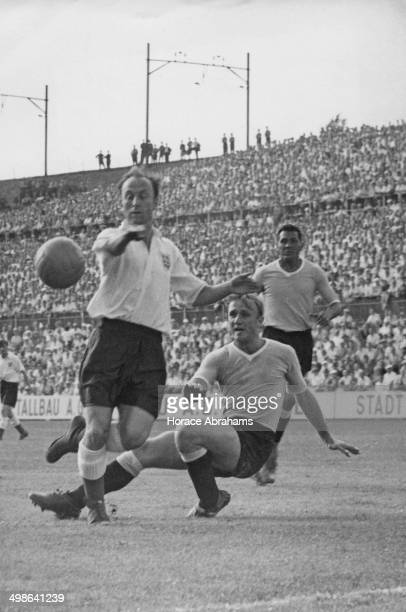 Ivor Broadis of England jumps over the outstretched leg of William Martinez of Uruguay in front of the Uruguayan goal during a World Cup quarterfinal...