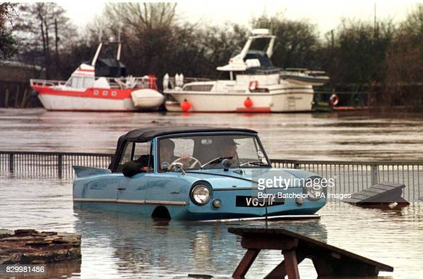 Ivor Newby from Bromsgrove drives his Amphicar with Peter Reeve through a flooded beer garden alongside the River Severn at UptonuponSevern today...