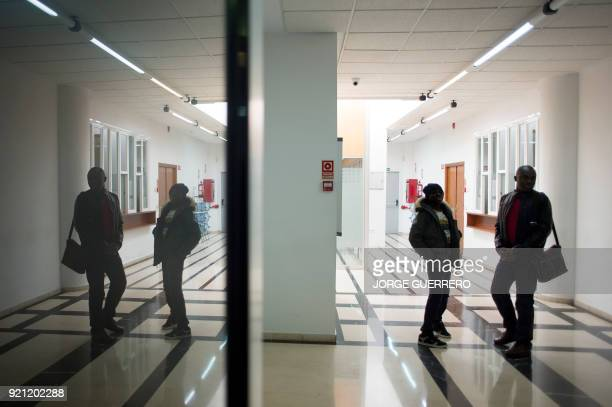 Ivorian Ali Ouattara and his son Adou wait in court before Ouattara's trial in Ceuta a Spanish overseas territory in northern Morocco on February 20...