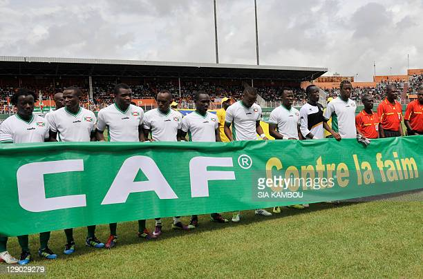 Ivorian and Burundian national team players pose on October 9 2011 at the Felix Houphouet Boigny stadium in Abidjan with a banner reading...