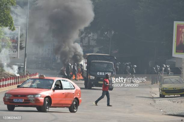 TOPSHOT Ivorian antiriot Police arrive to disperse young demonstrators that burnt barricades in the road during a protest against the third term of...