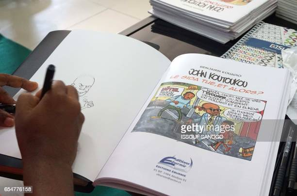 Ivorian cartoonist Benjamin Kouadio signs one of his book during the newspaper cartoon and comic books festival Coco Bulles on March 18 2017 in...