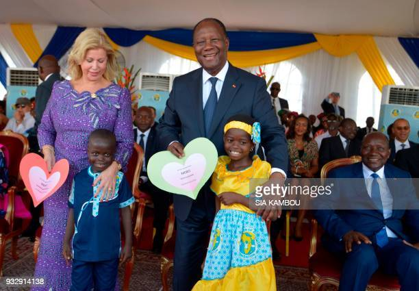 Ivorian First Lady Dominique Ouattara and Ivorian President Alassane Ouattara pose with children during the inauguration of the Mother-Child Hospital...
