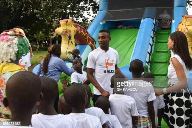 Ivorian football player Salomon Kalou plays with orphans during a Christmas event in Abidjan on December 22 2017 The Kalou Foundation founded by...
