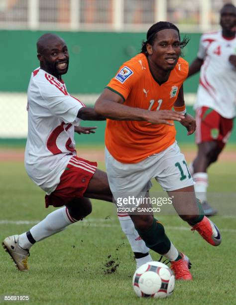 Ivorian National football team 'Elephants' striker Didier Drogba duels for the ball with Malawi team captain Peter Mponda on March 29 2009 at Felix...