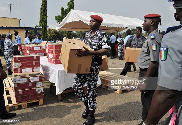 Ivorian police carry boxes containing 500 automatic guns given by France on November 16 2013 at the Abidjan Police Training School in the Ivorian...