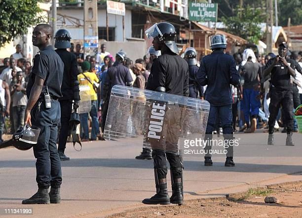 Ivorian policemen disperse protesters on a street of Gagnoa on November 29 a day after Ivory Coast's presidential elections second round vote marred...