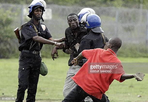 Ivorian policemen try to prevent demonstrators from throwing stones to French gendarmes 05 October 2004 during a protest at the French military...