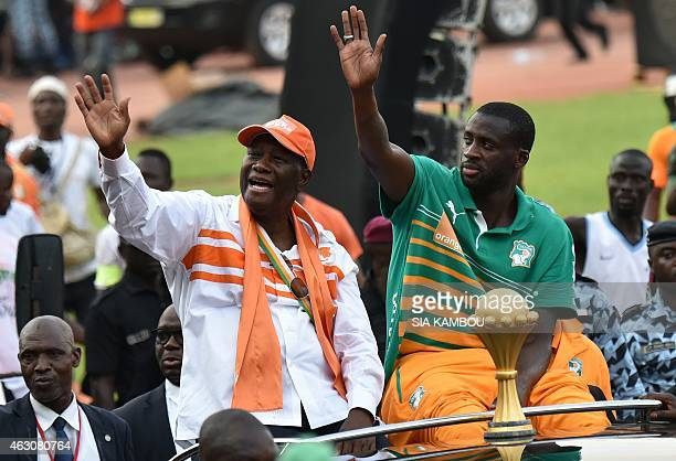 Ivorian President Alassane Ouattara and Ivory Coast's midfielder and captain Yaya Toure wave at the crowd during a welcoming parade in Abidjan on...