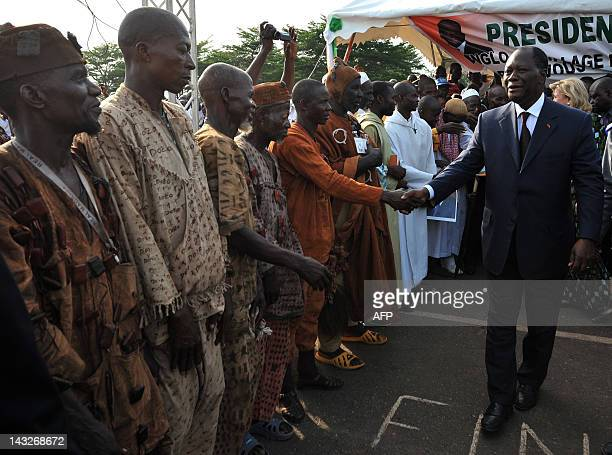 Ivorian President Alassane Ouattara meets traditional hunters called 'Dozo' upon his arrival on April 22 2012 in Guiglo prior to a meeting Ouattara...