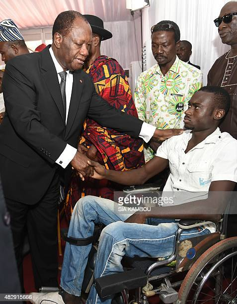Ivorian President Alassane Ouattara shakes hands with a man who was disabled after being wounded during the 20102011 postelection violence as a...
