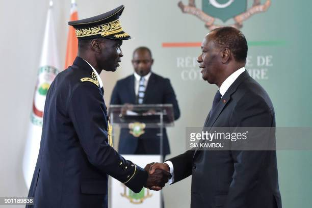 Ivorian President Alassane Ouattara shakes hands with Chief of staff of the Armed forces of Ivory Coast general Sekou Toure , after a New Year wishes...