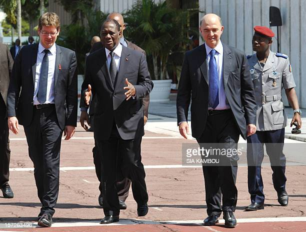 Ivorian president Alassane Ouattara walks with French Finance minister Pierre Moscovici and Development Aid Minister Pascal Canfin on December 1 2012...