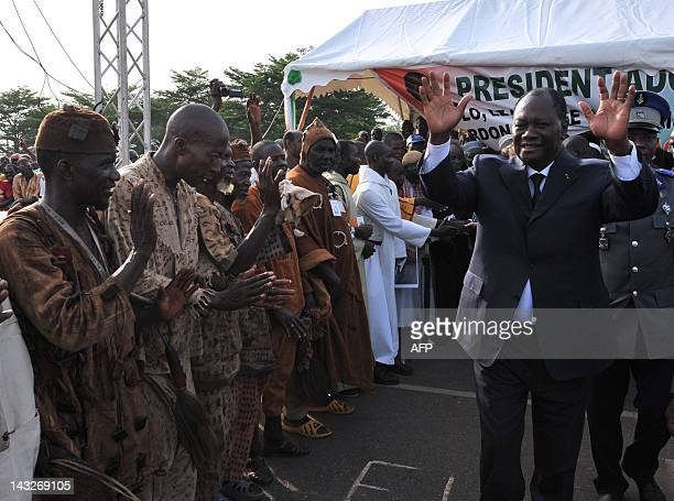 Ivorian President Alassane Ouattara waves as he meets traditional hunters called 'Dozo' upon his arrival on April 22 2012 in Guiglo prior to a...