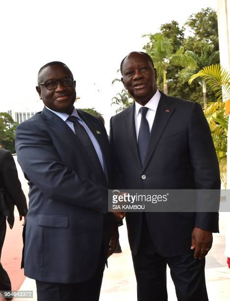 Ivorian President Alassane Ouattara welcomes Sierra Leone president Julius Maada Bio prior to a meeting on May 4, 2018 at the presidentaial palace in...