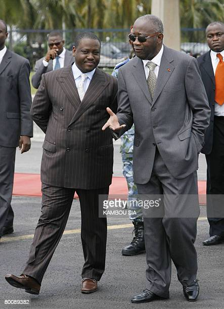 Ivorian President Laurent Gbagbo speaks with Ivorian Prime Minister Guillaume Soro as they await the arrival of new Sierra Leone President Ernest Bai...