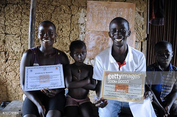 Ivorian refugee Zeade Gnolo Alex Bernadin his wife and two kids pose with certificates they obtained while working for the UNHCR at the PTP refugee...