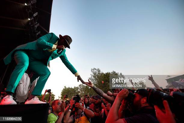 Ivorian singer Alpha Blondy greets fans as he performs on stage during the 31st Eurockeennes rock music festival in Belfort, eastern France, on July...