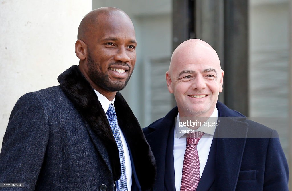 Ivorian soccer player Didier Drogba (L) and FIFA President Gianni Infantino (R) pose upon their arrival at the Elysee Palace to attend a lunch meeting with French President Emmanuel Macron and Liberian President George Weah on February 21, 2018 in Paris, France. Weah is on two days official visit in France.