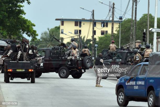 Ivorian soldiers and gendarmes patrol in their vehicle by Ivory Coast's army headquarters the Gallieni military camp in Abidjan on May 12 2017 as...
