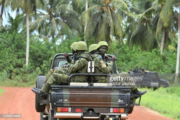 Ivorian soldiers drive on the back of a vehicle outside the International Academy for Combating Terrorism in Jacqueville in Ivory Coast on June 10,...