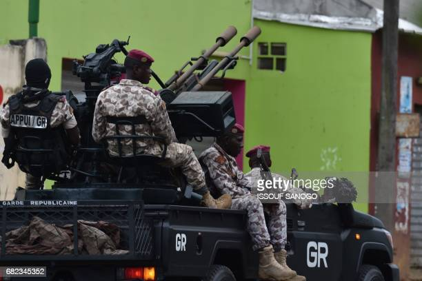 Ivorian soldiers patrol in their vehicle by Ivory Coast's army headquarters the Gallieni military camp in Abidjan on May 12 2017 as they fired shots...