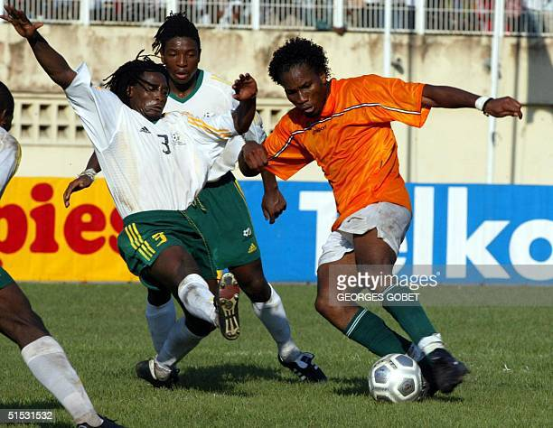 Ivorian striker Didier Drogba is challenged by South African defender Jacob Lekgetho O8 September 2002 at the Houphouet Boigny stadium in Abidjan...