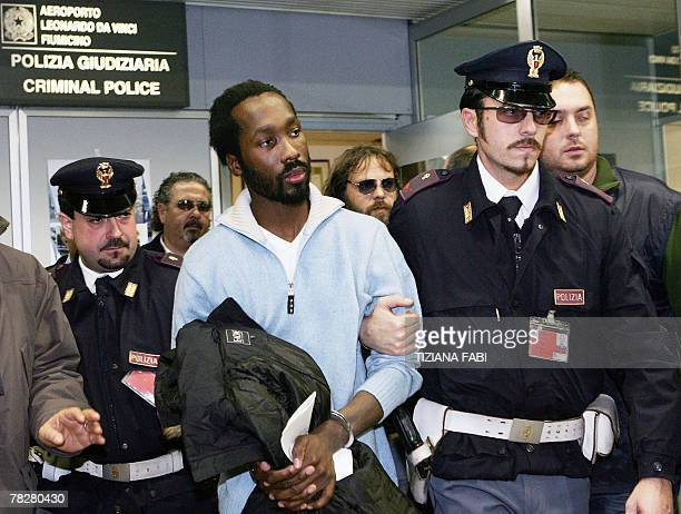 Ivorian suspect in the murder of a British exchange student Rudy Hermann Guede is escorted by police officers as he arrives at Rome's Fiumicino...