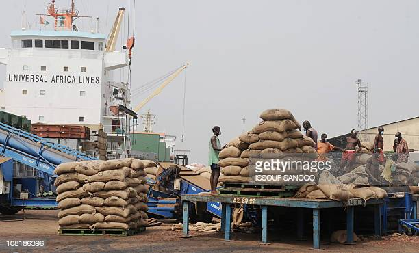 Ivorian workers stand on a plateform with bags of cocoa beans on January 18 2011 at the Port of Abidjan where 80% of Ivory Coast's exports transit...