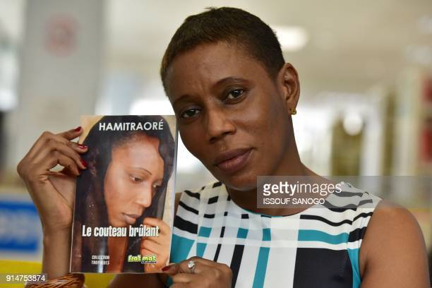 Ivorian writer Hami Traore poses with her book Le couteau brulant in which she tells the story of her genital mutilation in the region of Bouake at...