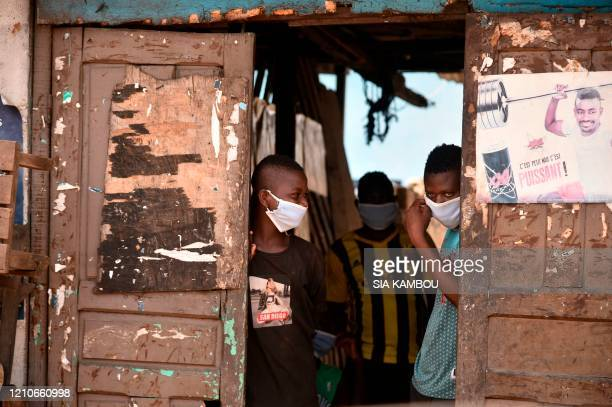 Ivorian youth wearing masks as a protective measure against the spread of the COVID-19 coronavirus looks from a door on APril 22, 2020 as Ivorian...