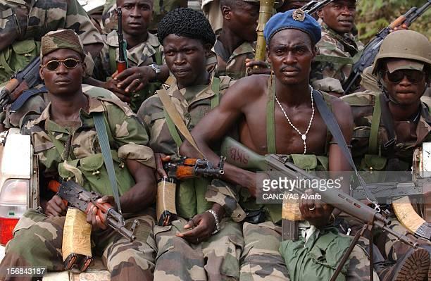 Ivory Coast At The Edge Of Chaos Miliciens libériens de l'armée loyaliste assis avec leurs armes à l'arrière d'un pickup dans les rue de TOULEPLEU à...