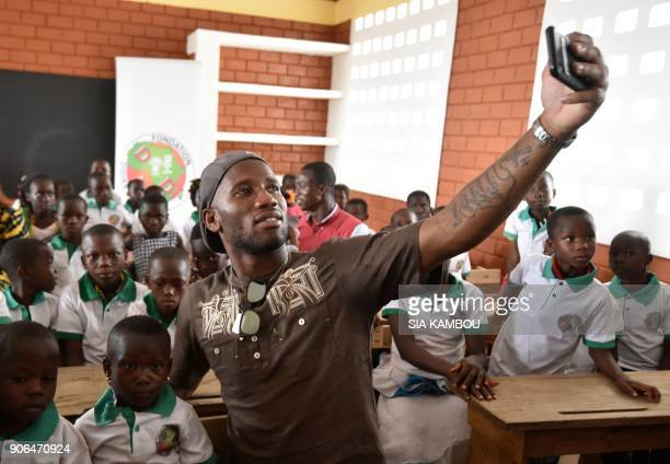 Ivory Coast international forward Didier Drogba takes a selfie video with pupils during the inauguration of an elementary school named after him on...
