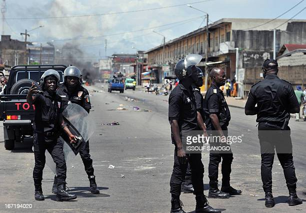 Ivory Coast policemen stand after dispersing supporters of Cisse Bacongo one of the candidates to the municipal elections in Koumassi on April 22 in...