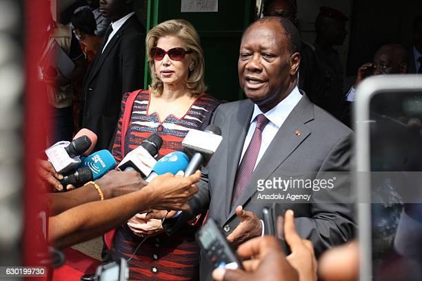 Ivory Coast President Alassane Ouattara and his wife Dominique Folloroux-Ouattara speak to media after casting their votes during the parliamentary...
