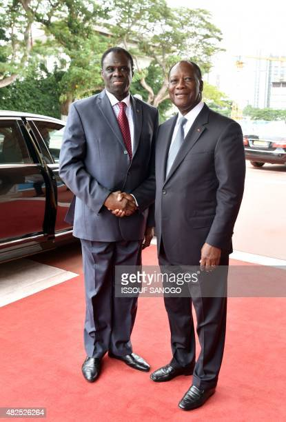 Ivory Coast president Alassane Ouattara shakes hands with Burkina Faso's transitional president Michel Kafando at the presidential palace in Abidjan...