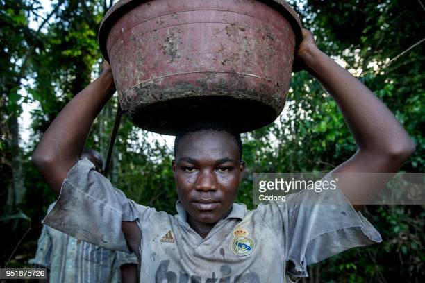 Ivory Coast Young farmer carrying harvested cocoa pods