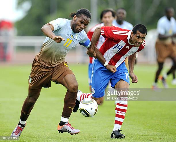 Ivory Coast's captain Didier Drogba fights for the ball with Paraguay's defender Paulo Da Silva during the International friendly football match...