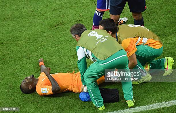 Ivory Coast's defender Arthur Boka is helped by medics during a Group C football match between Ivory Coast and Japan at the Pernambuco Arena in...