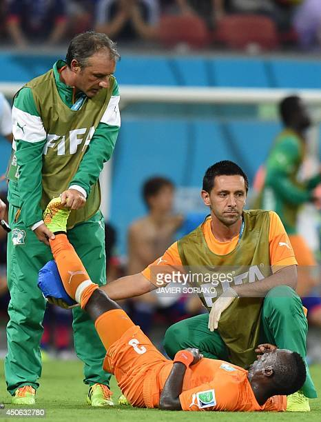 Ivory Coast's defender Arthur Boka is treated by medial staff during a Group C football match between Ivory Coast and Japan at the Pernambuco Arena...
