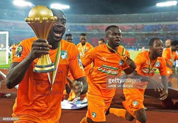 Ivory Coast's defender Kolo Toure raises the trophy as he celebrates with teammates after winning the 2015 African Cup of Nations final football...