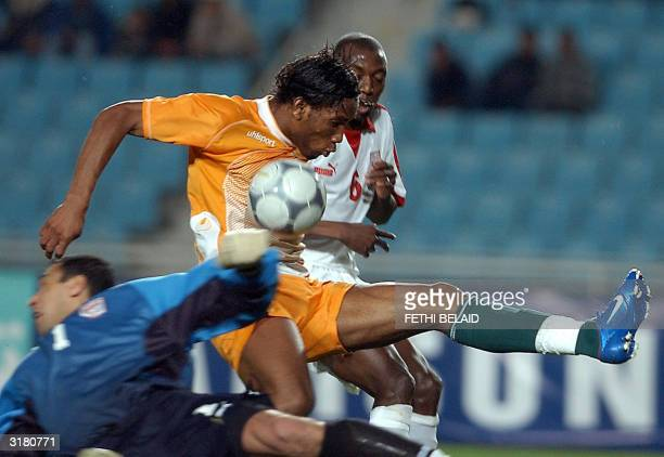 Ivory Coast's Didier Drogba vies with two Tunisian players Ali Boumnigel and Hatem Trabelsi to score the first goal for Ivory Coast during their...